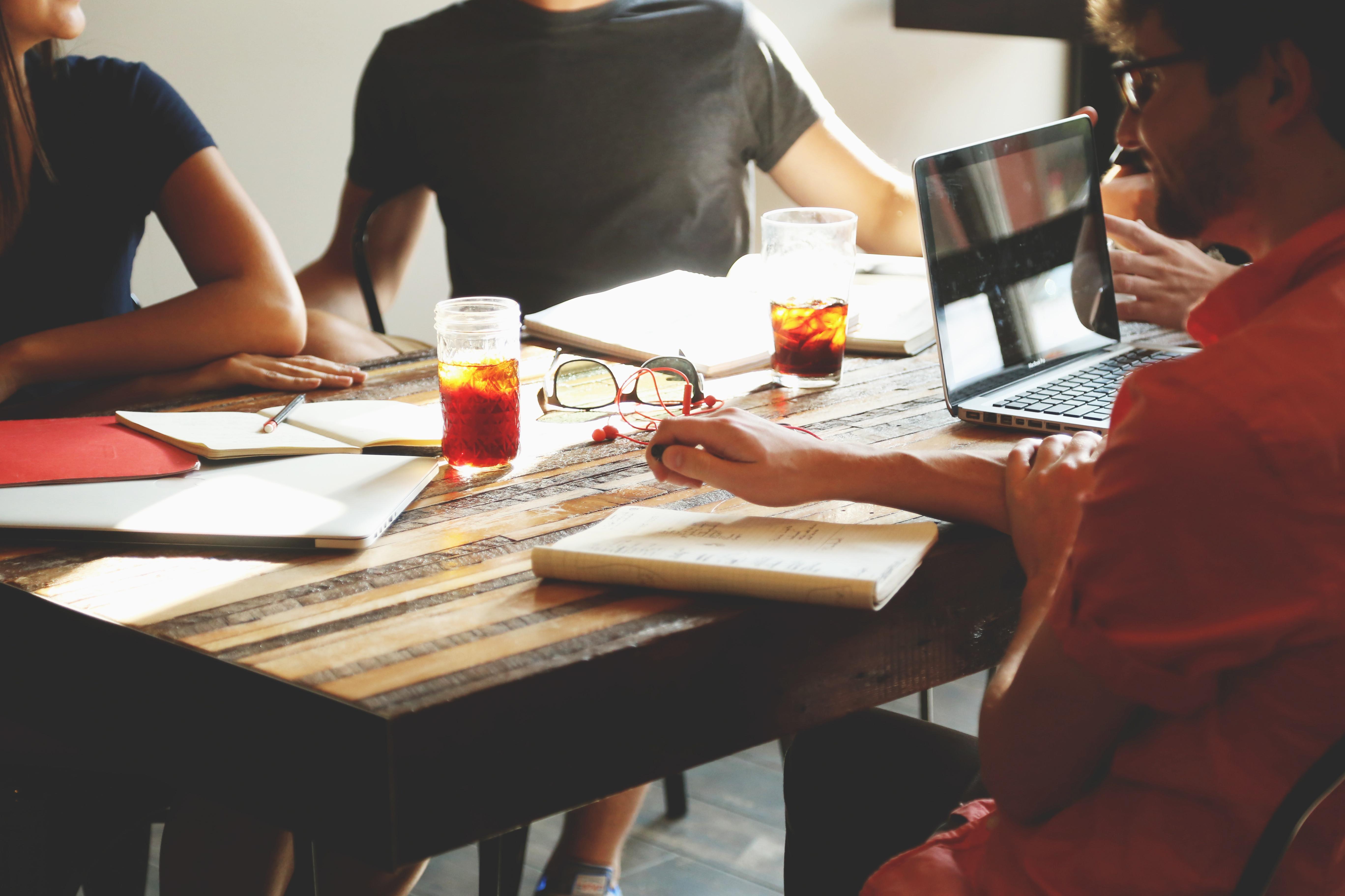 Drei Personen sitzen zu einer Besprechung des Themas Digital Asset Management am Tisch mit Getränken und Notizblöcken