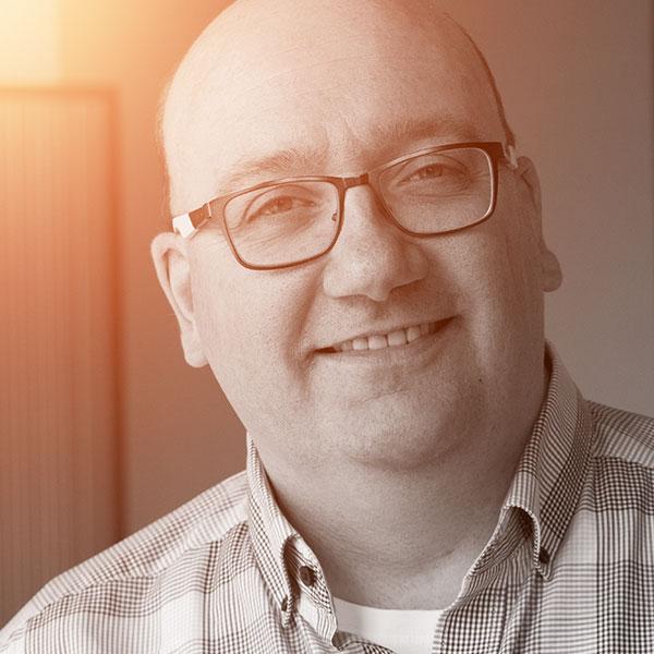Das Portrait zeigt einen lächelnden Mann mit Brille und kariertem Hemd