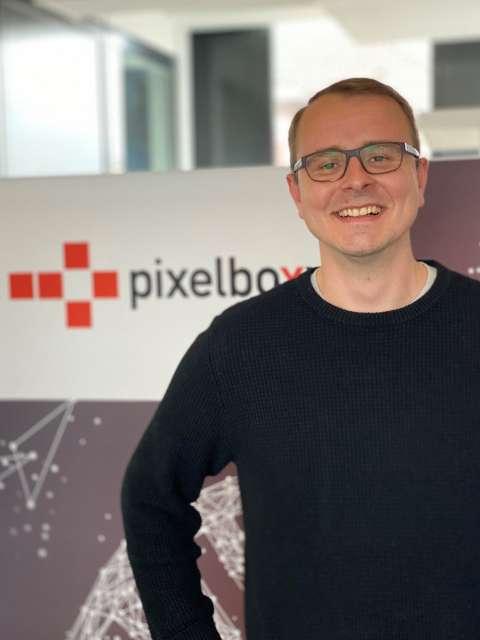 Ein junger Mann mit dunklem Pullover und Brille steht lächelnd vor einem Pixelboxx Aufsteller